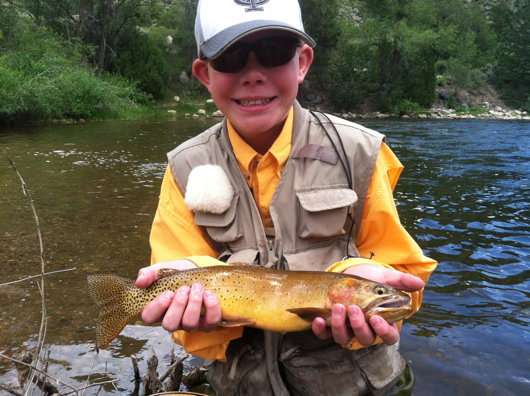 NoCo Youth Day Camper Tommy shows off a cutthroat from the Poudre.